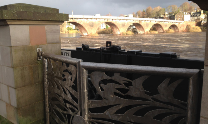 The gates have been closed afterheavy rain caused the river Tay to rise in the city centre.