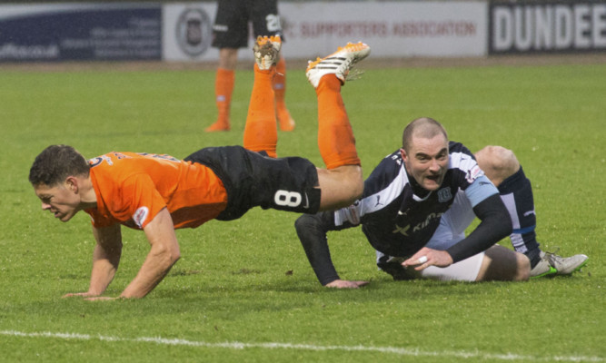 United's John Rankin is challenged by Dundee defender James McPake, who is injured in the process.