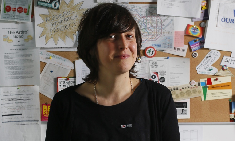 Badges of Honour exhibition at Glasgow Women's Library, Bridgeton. Pictured is artist Ellie Harrison in her studio wearing her badge. It is a 'Bring Back British Rail', a campaign that Ellie runs.