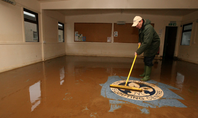 Bill McDonald, of North Angus District Scout Council, fights a losing battle against the flood water at the Jock Neish centre.