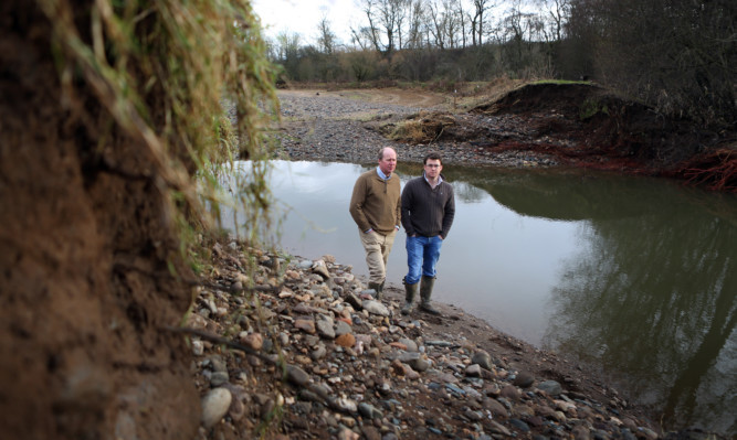 Bob and Rob Strachan in a stubble field at Lochlands Farm that was filled with stones and rubble when the River Ericht burst through banks designed to protect fields.