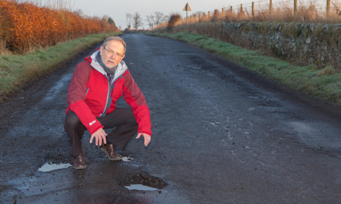 Councillor Tim Brett at the road near Kilmany where there is a reported 95 potholes.