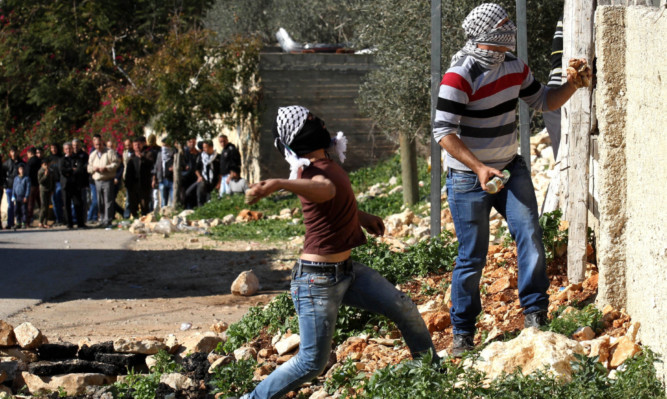 NABLUS, WEST BANK - DECEMBER 25: Palestinians throw stones to Israeli security forces during a protest against Israeli governments expropriate Palestinians lands at Kafr Qaddum village in Nablus, West Bank on December 25, 2015. (Photo by Nedal Eshtayah/Anadolu Agency/Getty Images)