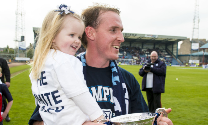 Gary Irvine with one of his daughters after Dundee won the Championship title.