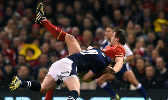 Finn Russell puts in a big hit on opposite number Dan Biggar in Saturday's 6 Nations match in Cardiff.