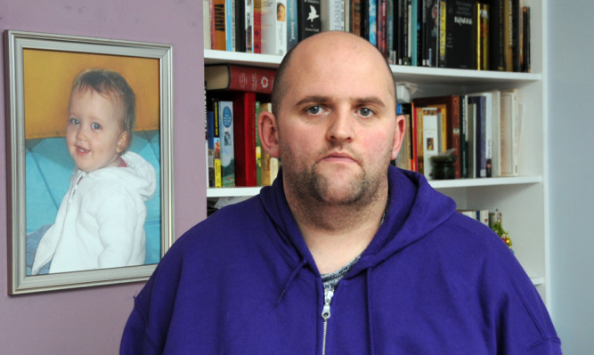 Alan Glynn with a photograph of his daughter who died from meningitis in 2011.