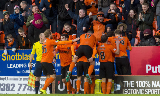 United's players unite with fans to celebrate Paul Paton's winner.
