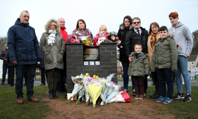 Family of the fishermen gathered around the memorial.