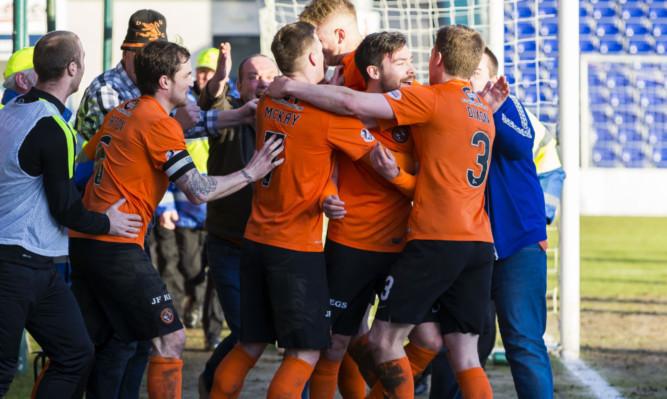 The jubilant United players celebrate Ryan Dow's goal.