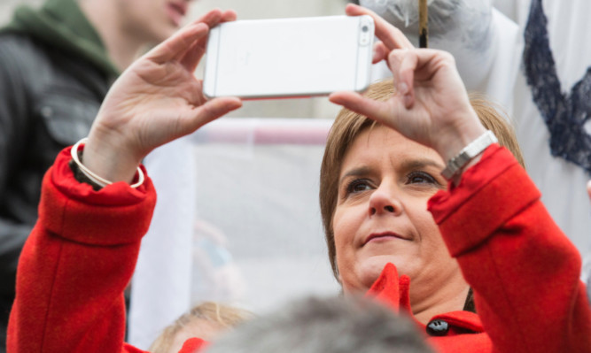 Nicola Sturgeon snaps a picture during the anti-Trident rally in London