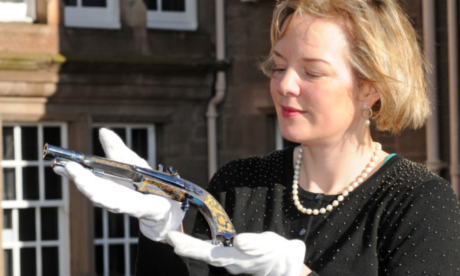 Katherine Wright, valuer and auctioneer with Bonhams holding one of the Highland 28-bore gold-inlaid flintlock pistols presented to the Marquess of Breadalbane.