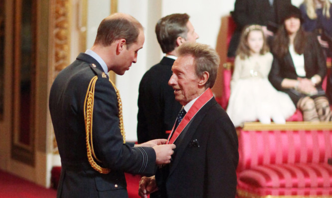 Former Scotland and Manchester United football great Denis Law is made a Commander of the Order of the British Empire by the Duke of Cambridge.