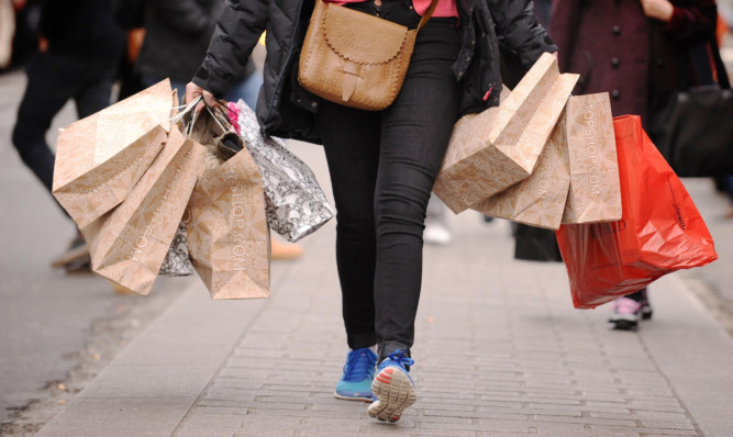 """File photo dated 6/12/11 of a shopper carrying shopping bags. High street sales dropped by 2.2% last month in an """"underwhelming"""" Christmas for many retailers, according to a report. ... High street sales ... 06-01-2014 ... London ... UK ... Photo credit should read: Dominic Lipinski/PA Wire. Unique Reference No. 18604411 ... Issue date: Monday January 6, 2014. Figures from accountancy firm BDO showed the sales surge hoped for by many shops failed to materialise in the crucial trading period, with like-for-like sales - excluding online trade - dropping by as much as 6.7% in the week to December 22. See PA story ECONOMY Retail. Photo credit should read: Dominic Lipinski/PA Wire"""