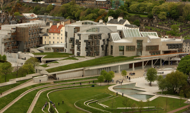 In this photo illustration, A man holds a Saltire flag outside the Scottish Parliament on May 6, 2009 in Edinburgh, Scotland. Today marks the 10th anniversary of the first Holyrood election polling day, before the Scottish Parliament gained full powers on July 1, 1999.