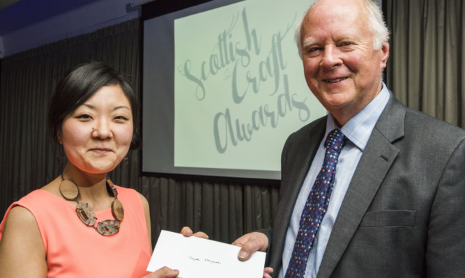 Robin Blair, chairman of the Inches Carr Trust, presents the award to Sayoko Kobayashi.