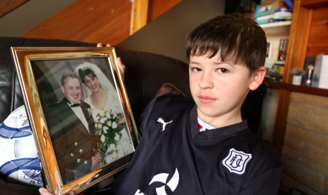 Gavin, 14, with a picture of his mother and father.