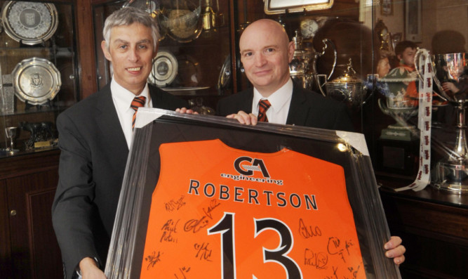 Derek Robertson (left) receiving a signed United strip from chairman Stephen Thompson.