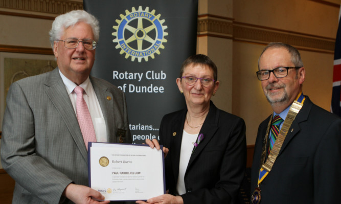 Mr Burns receives his Paul Harris Fellowship for work with amputees like Naduni, below, from Dr Janet Lowe, chairman of District 1010, and president David Laing.