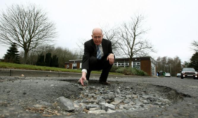 Mr Wilson at the pothole.