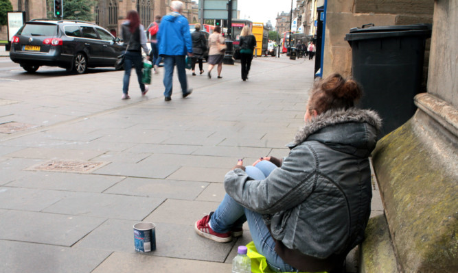 A woman begs for money from passersby in the centre of Dundee.