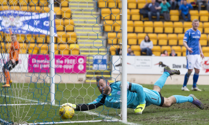 Alan Mannus tries in vain to keep Ryan Dow's shot out.
