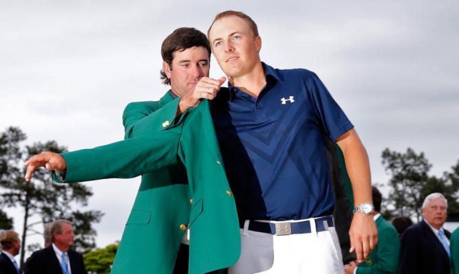 Bubba watson helps Jordan Spieth into the Green Jacket last year.