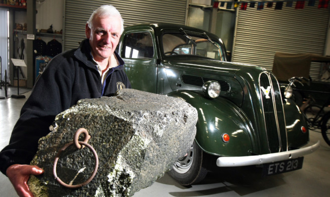 Kris Miller, Courier, 06/04/16. Picture today at Strathmore Vintage Vehicle Club where a Ford Popular, similar to the one that stole the Stone of Destiny is on display, complete with the clubs very own stone. Pic shows Allan Burt, Chairman of SVVC with the stone and car.