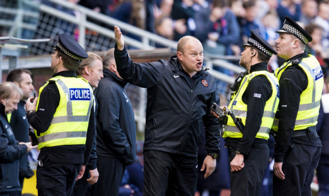 Dundee United manager Mixu Paatelainen is spoken to by police officers during the last Dundee derby.