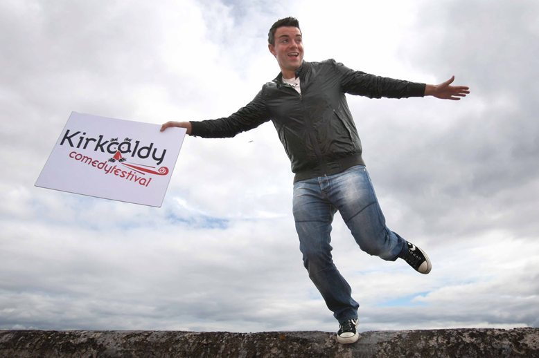 Kris Miller, Courier, 03/08/10, News. Picture today outside the Mercat shopping centre, Kirkcaldy. Comedian Des Clarke was in town to open the Kirkcaldy Comedy Festival today, Pic shows Des on the sea wall with Kirkcaldy Comedy Festival sign.