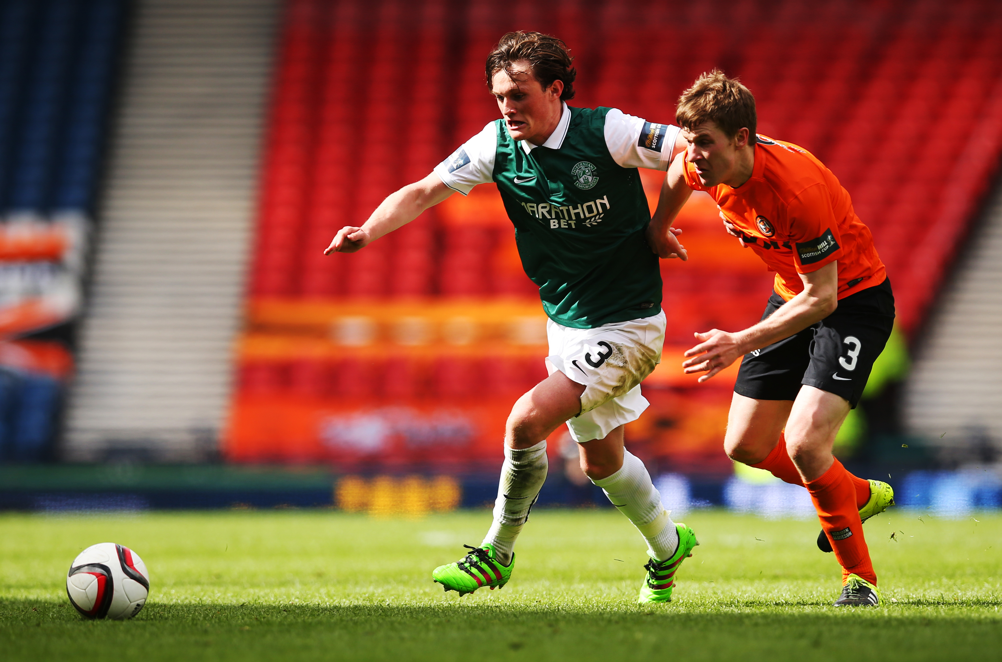 Liam Henderson of Hibernian vies with Paul Dixon of Dundee United during the Scottish Cup semi-final.