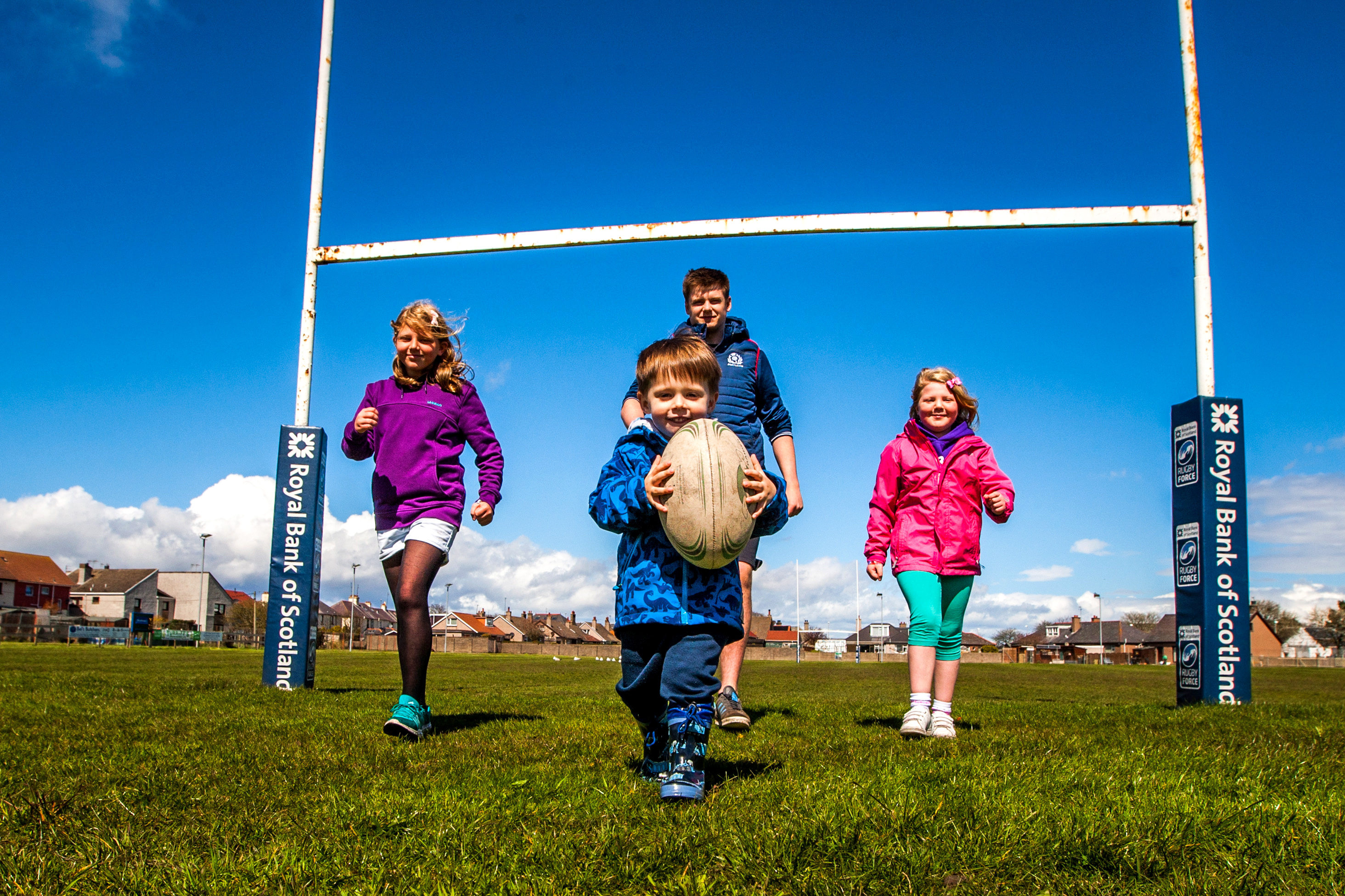 Three-year-old Caleb MacPherson alongside Aimee Webster and her sister Tracey with Montrose Rugby Club community coach Thomas Lindsay.