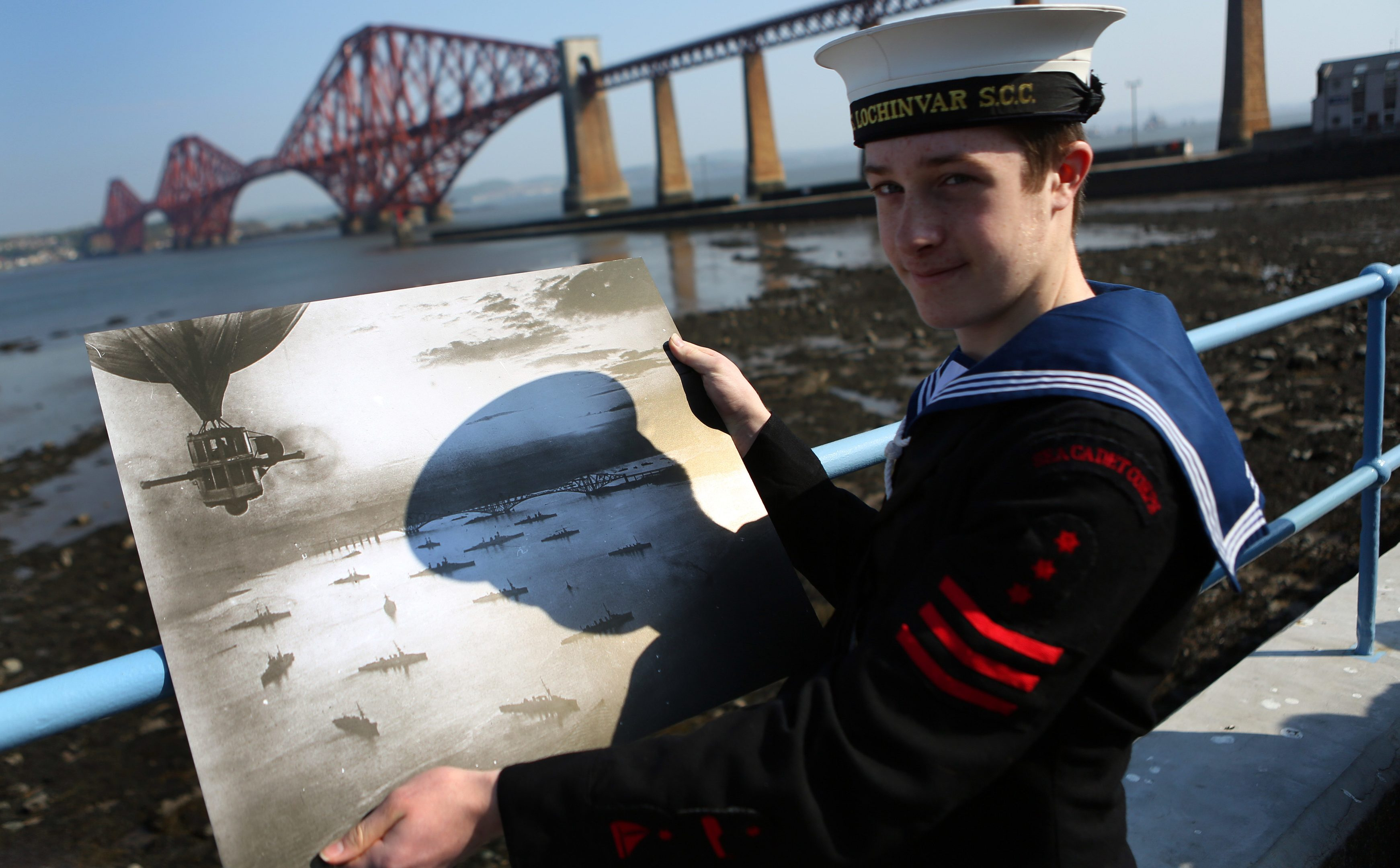 Sea Cadet Murray George with his shadow cast over a picture of the fleet on the river around 1916.