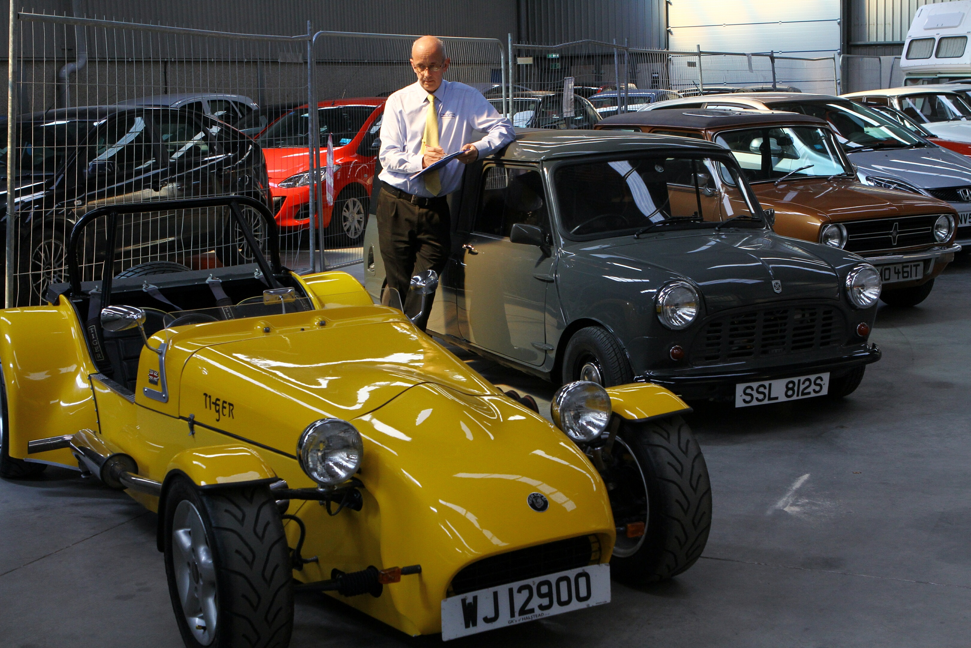 Auction manager Keith Murray takes down the particulars of a Tiger Cat E1, with an immaculate Mini 95 pickup in the background at Morris Leslie's, Errol.