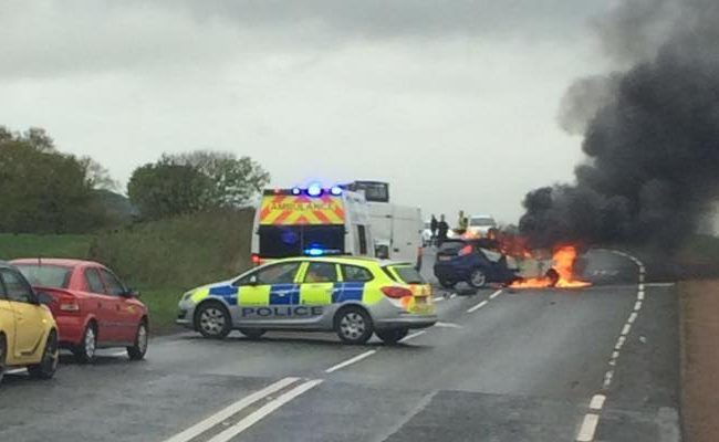 The Ford Fiesta on fire following Saturday morning's crash on the A909 in Fife.