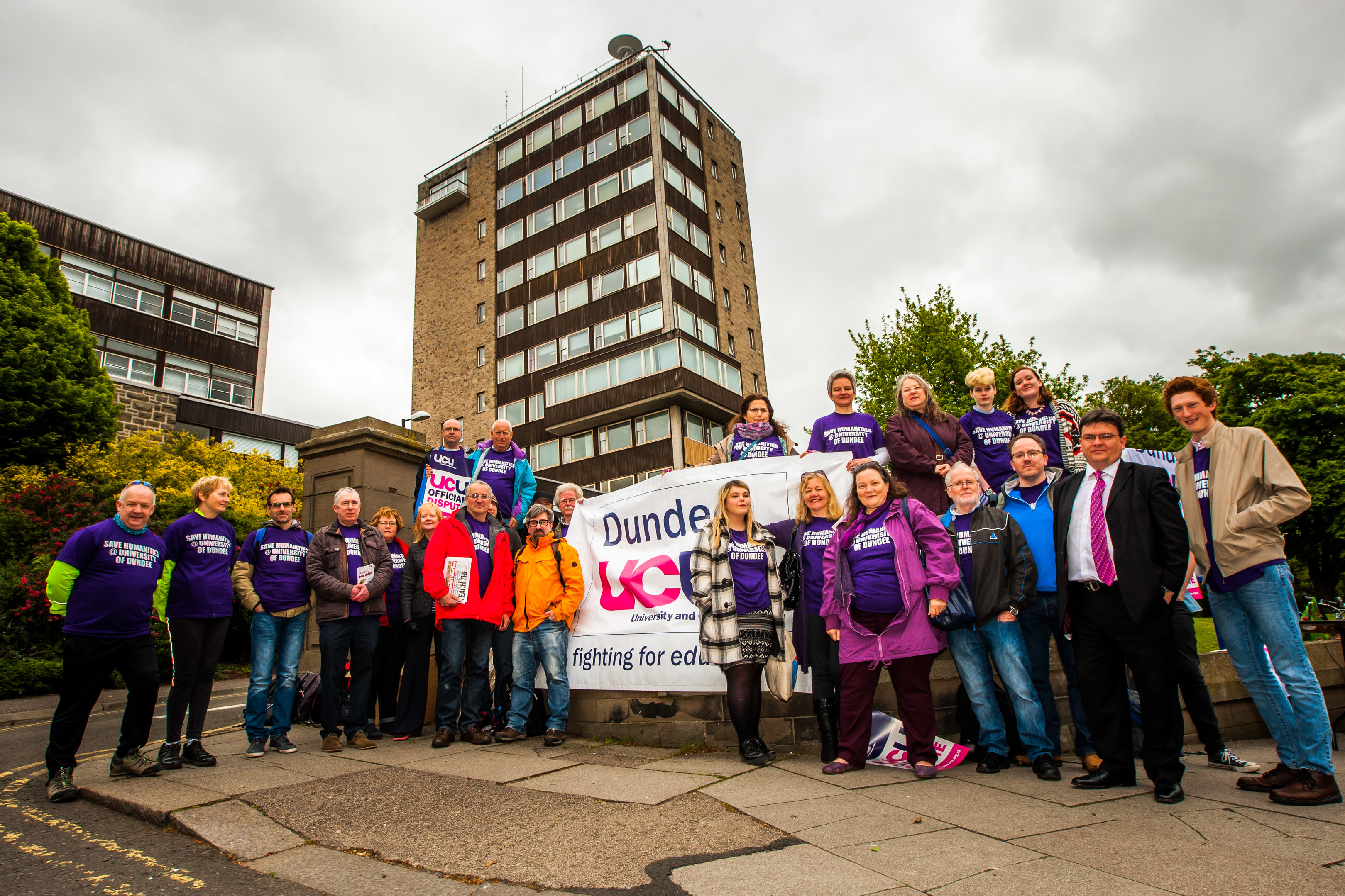 Demonstrators gather outside Dundee University's tower building.