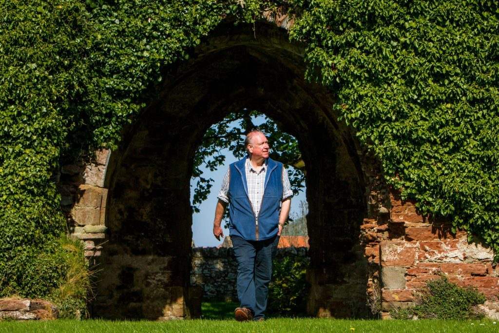 Drew McKenzie Smith walks through the remains of the Abbeys east gate where William Wallace once strode