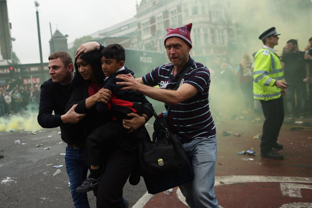 LONDON, ENGLAND - MAY 10: A woman and a child are helped past West Ham fans as people become violent and start throwing bottles at police outside the Boleyn Ground on May 10, 2016 in London, England. Tonights Premier League match against Manchester United is West Ham United's last game at the Boleyn Ground, bringing to an end 112 years of the club's history at the ground. The club will move into the Olympic Stadium next season, making way for developers and plans for 800 new homes where the stadium now stands. (Photo by Dan Kitwood/Getty Images)