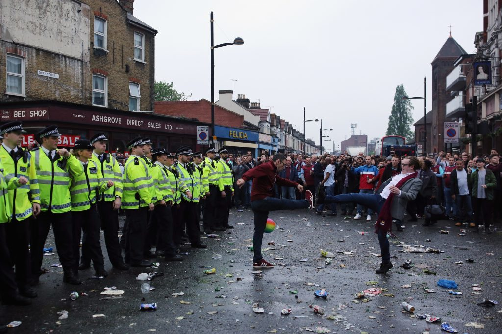LONDON, ENGLAND - MAY 10: Police officers form a barrier after West Ham fans became violent and threw projectiles at police outside the West Ham United FC's Boleyn Ground on May 10, 2016 in London, England. Tonights Premier League match against Manchester United is West Ham United's last game at the Boleyn Ground, bringing to an end 112 years of the club's history at the ground. The club will move into the Olympic Stadium next season, making way for developers and plans for 800 new homes where the stadium now stands. (Photo by Dan Kitwood/Getty Images)