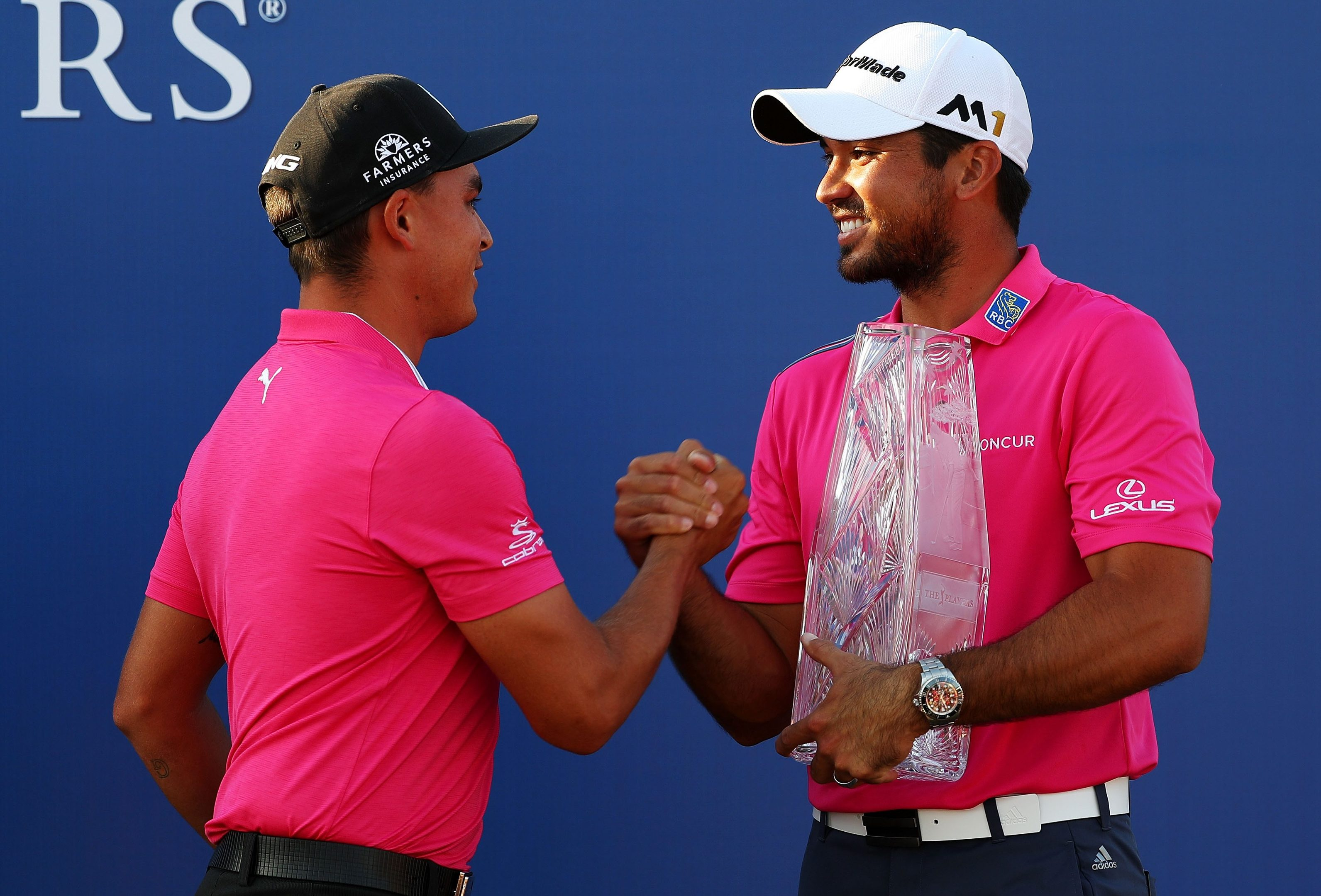 Last year's winner Rickie Fowler (left) presents the trophy to Jason Day.