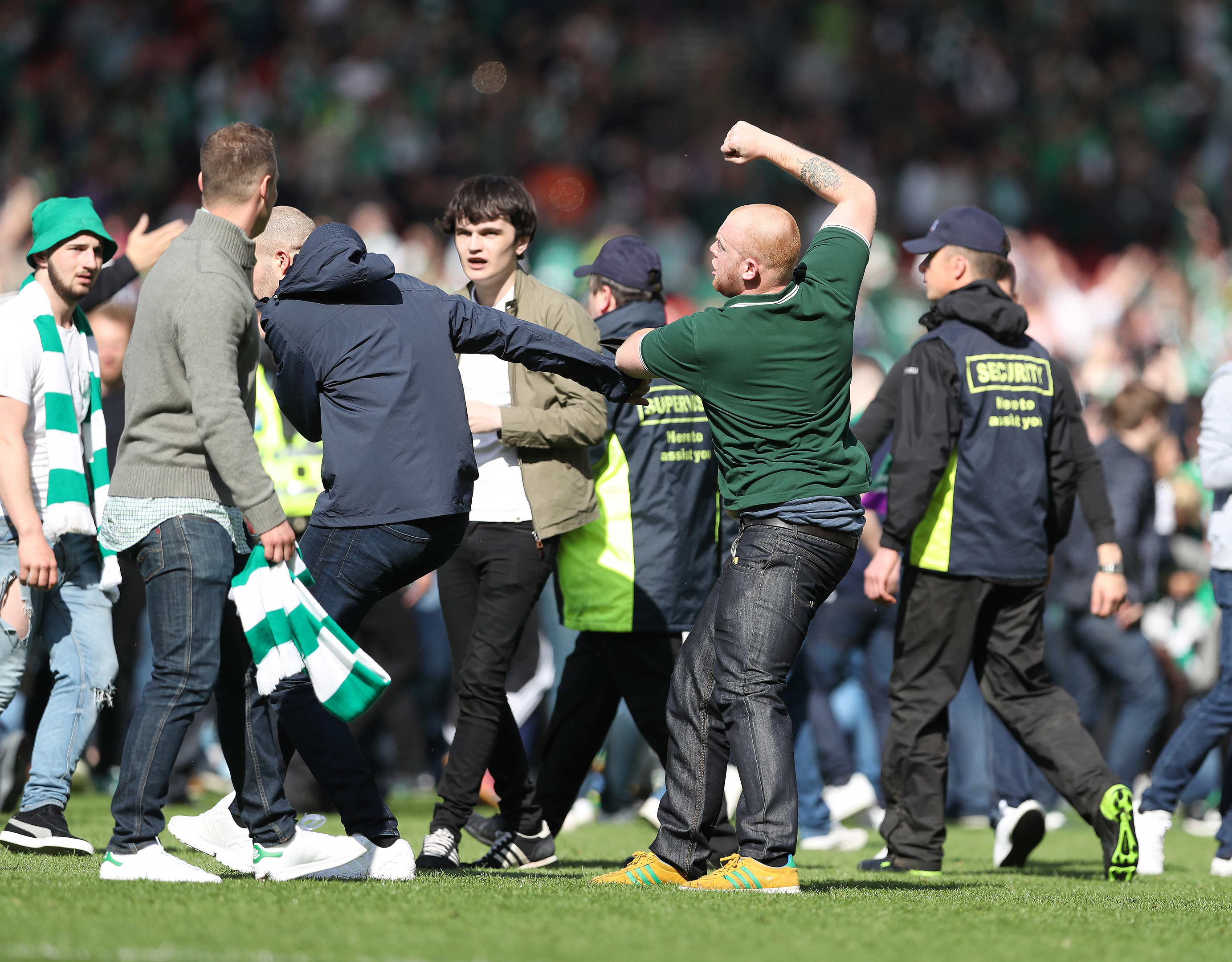 Hibs and Rangers fans fight as they invade the pitch after the Scottish Cup final.