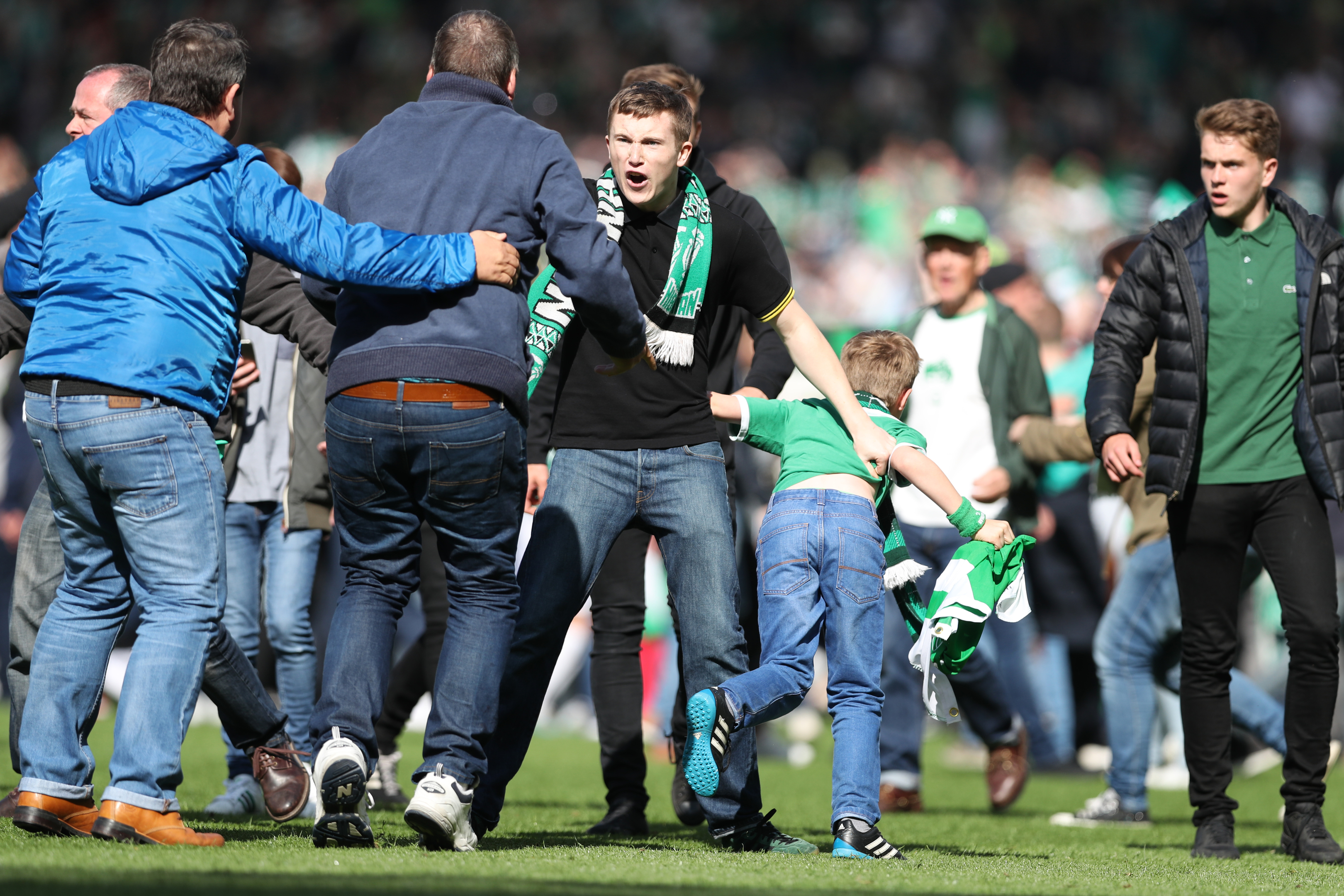 Fans fight after the pitch is invaded the after the Scottish Cup final .