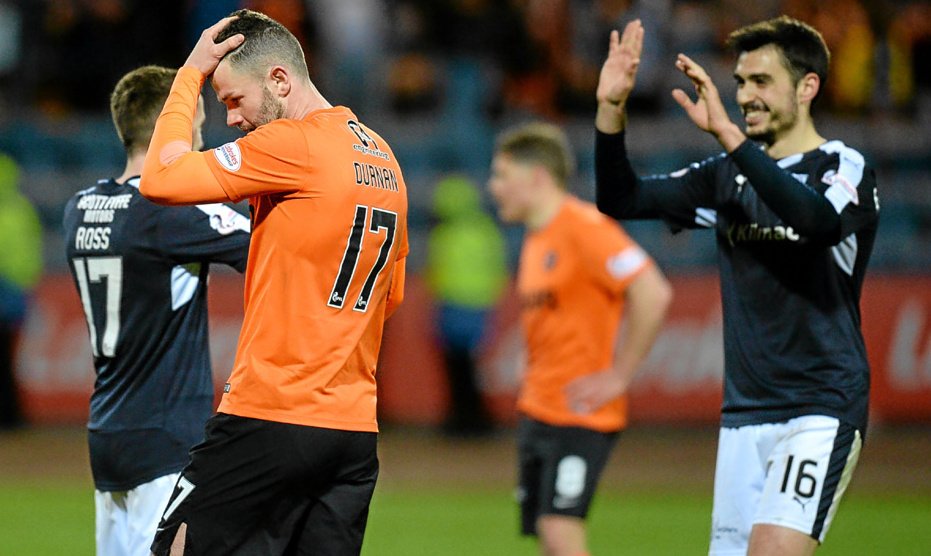 Dejection for Dundee United's Mark Durnan contrasts with celebration for Dundee's players.