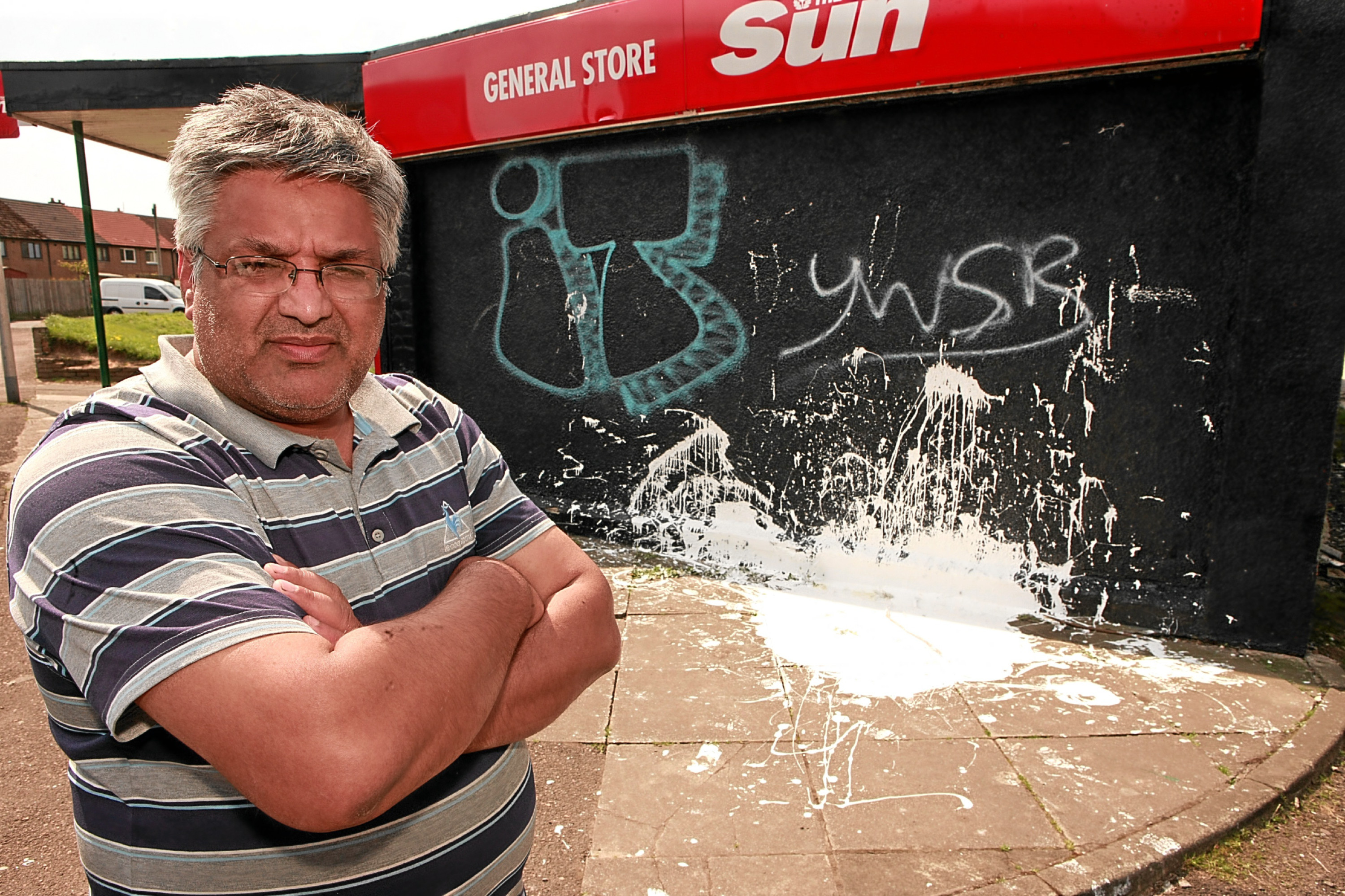 Ismal Din outside the vandalised shop in Fintry.