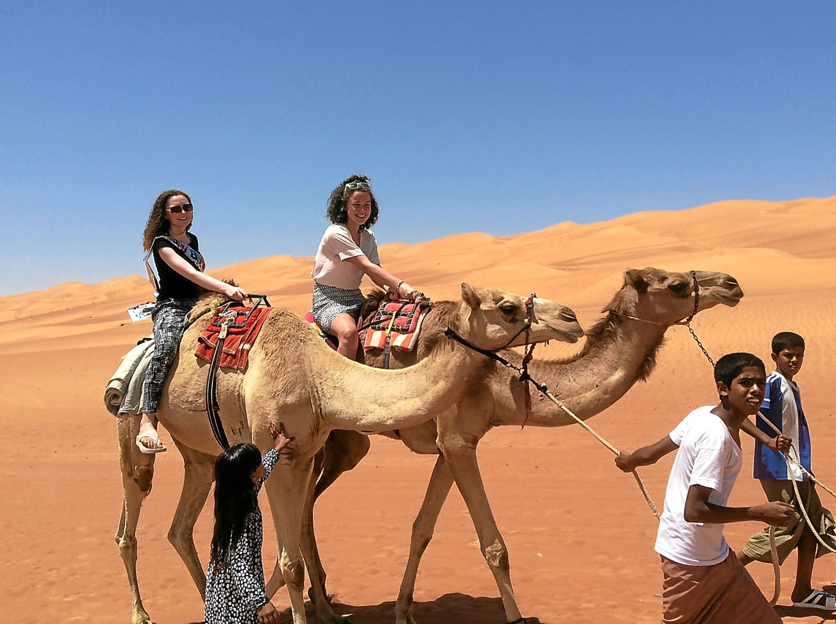 Pupils Abigail Johnston, left, and Zoe Morton, right, enjoy a camel ride.