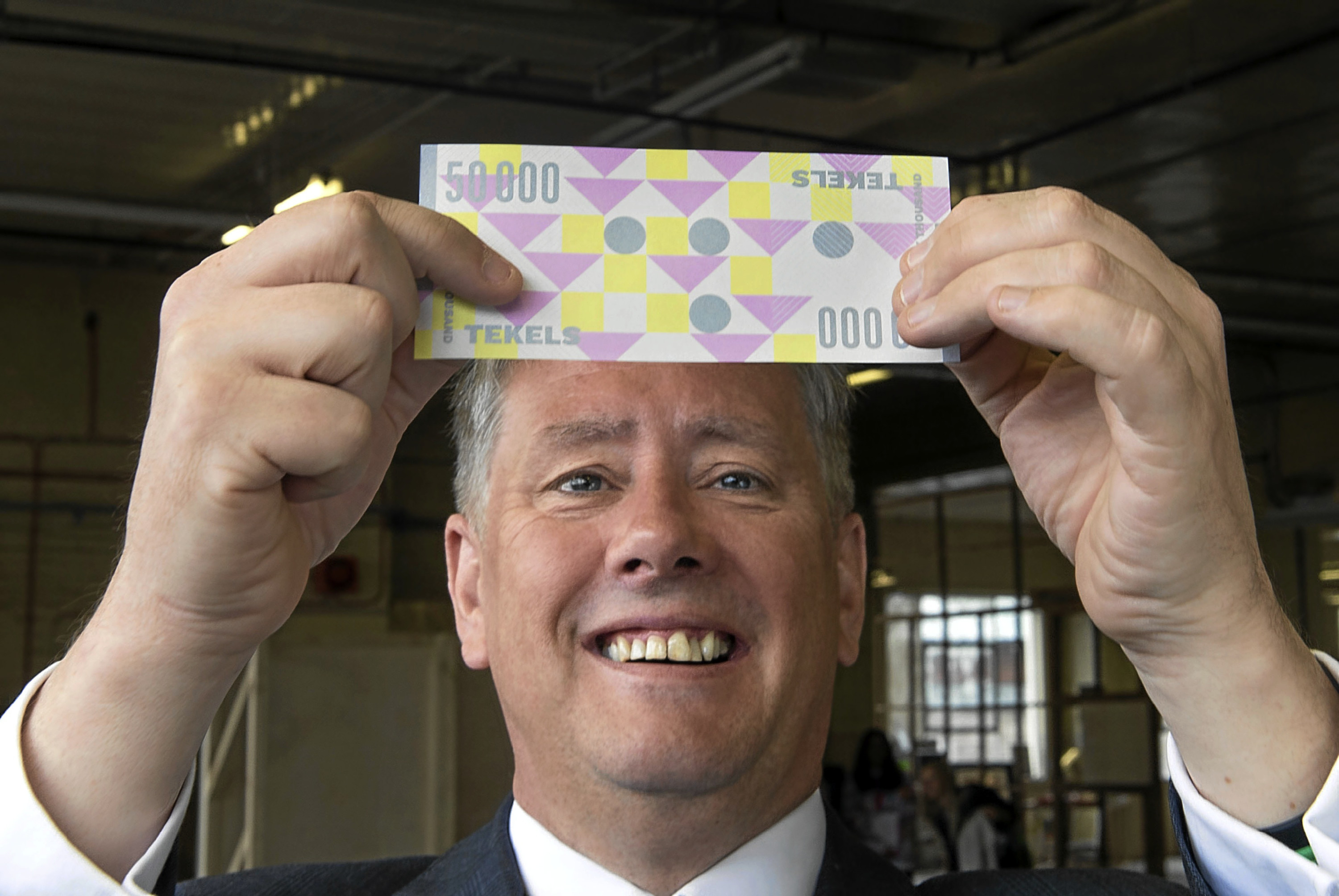 "Economy minister Keith Brown with a ""Tekel"" banknote."