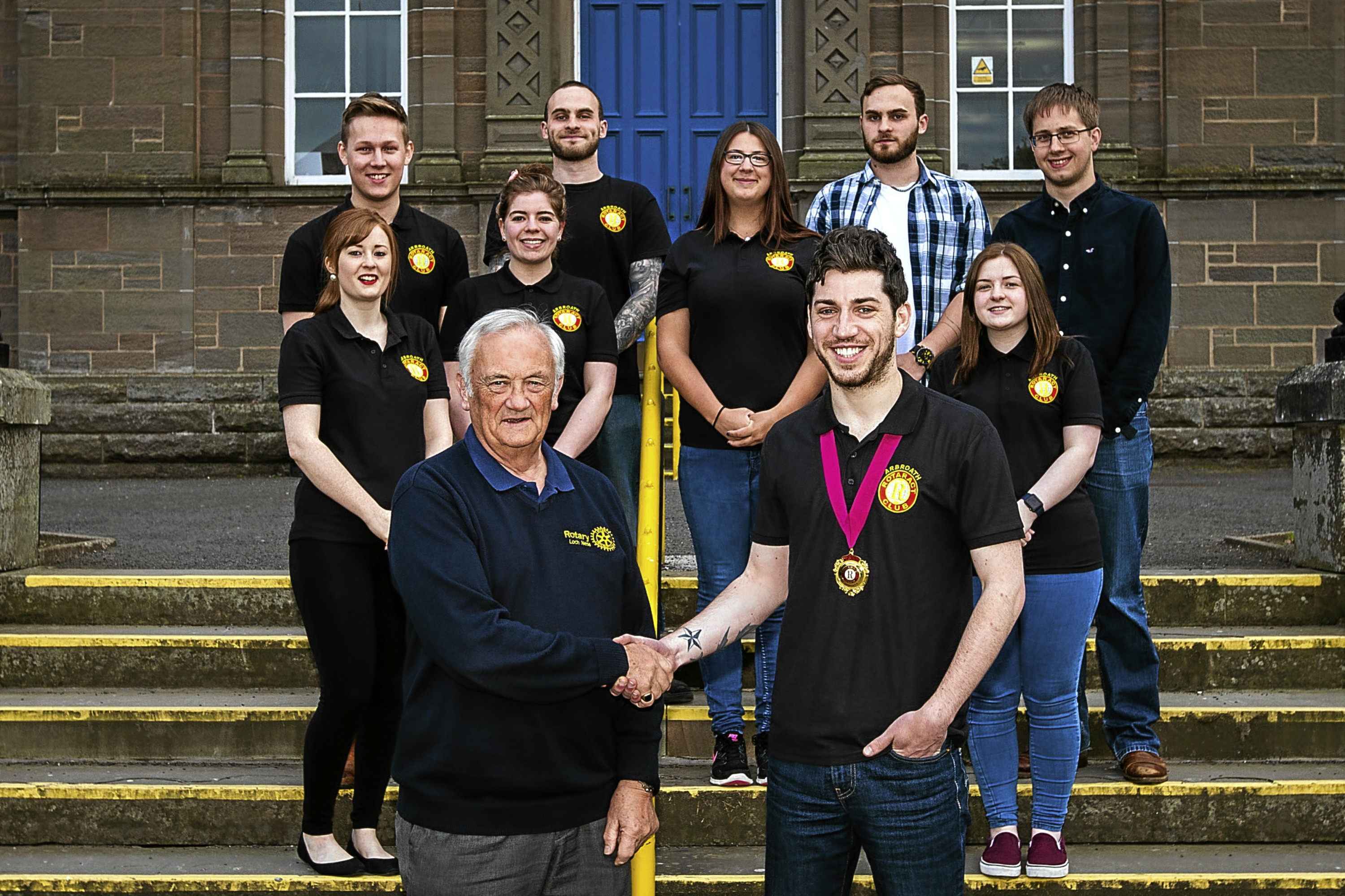 Mike Halley shakes hands with Arbroath Rotaract president Callum Fairweather