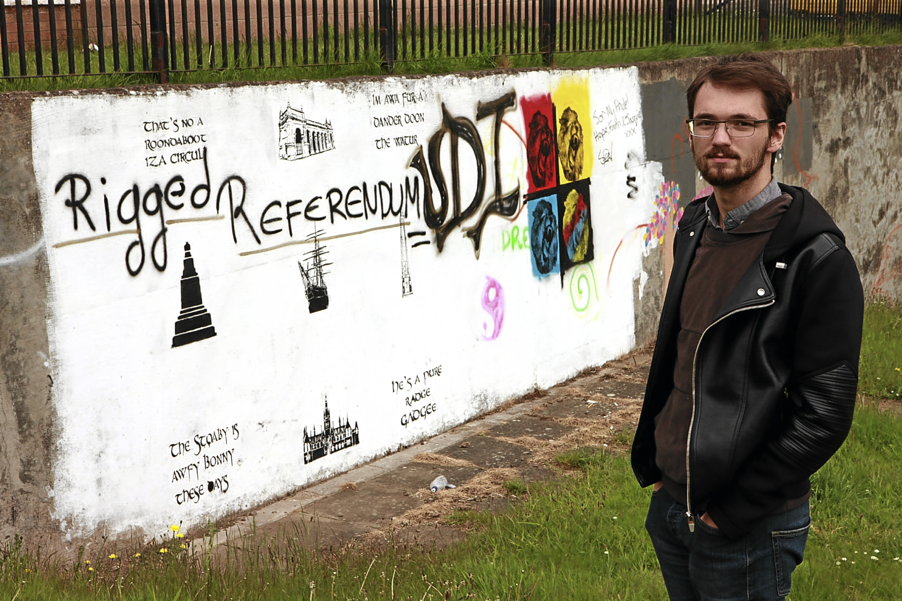 Connor Beaton beside the grafitti on the wall at Taybank Medical Centre.
