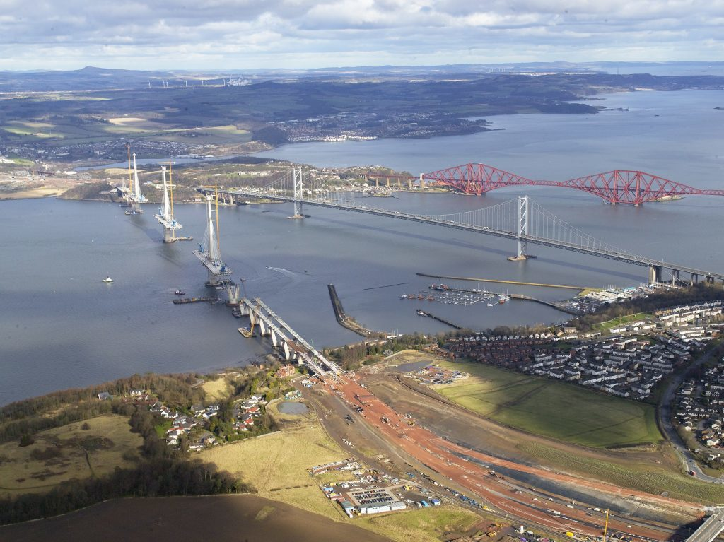 An aerial view showing the Queensferry Crossing under construction with the Forth Road Bridge and Forth Rail Bridge visible to the rear