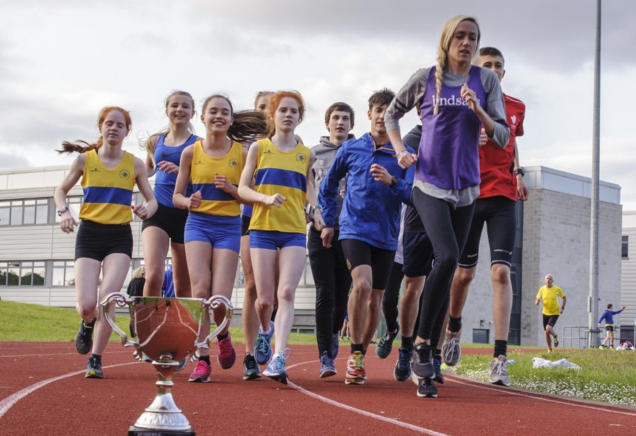 Eilish with Giffnock North AAC athletes at training at Williamwood High School, Glasgow, and the Lindsays Trophy.