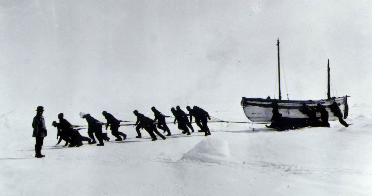 The crew hauling the James Caird across the Antarctic wastes after their ship the Endurance broke up, with Shackleton looking on.